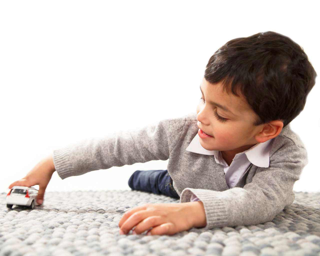 boy playing with car on grey carpet felt